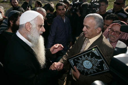 Rabbi Menachem Froman and Muslim cleric stand with copies of the Koran at a roadblock near Nablus  in apology for vandalism at a mosque