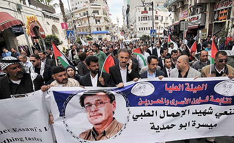 Palestinians rallying with portraits of Maysara Abu Hamdiyeh in Ramallah.
