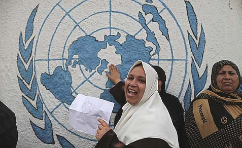 An Arab woman holding her refugee ration card during a protest outside the United Nations Relief and Works Agency (UNRWA) in Gaza City, April 8, 2013.