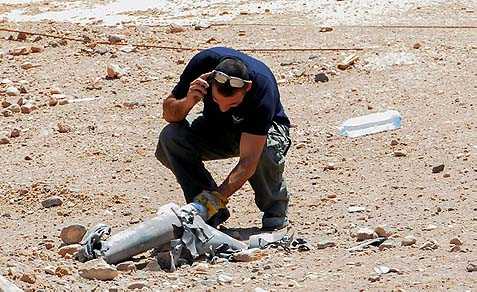 An Israeli police sapper examines exploded remains of a rocket fired at the Red Sea resort city of Eilat. April 17, 2013.