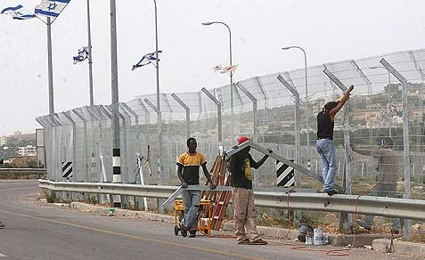 Arab workers erecting the security outside Gilo, in Jerusalem.