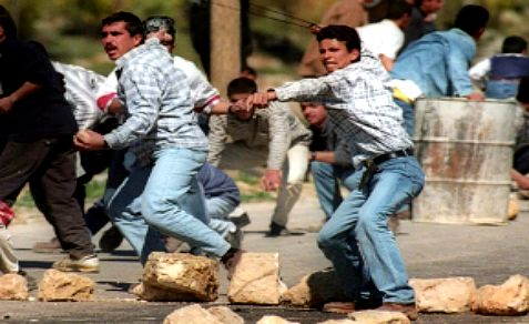 A Palestinian Arab winds up a slingshot before throwing a rock towards Israeli soldiers.