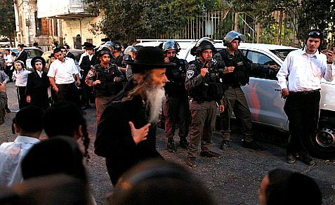 Riot police patrol Mea Shearim Tuesday after a mob of radical Haredim attacked a Haredi soldier