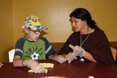 Liad shapes challah with his mother
