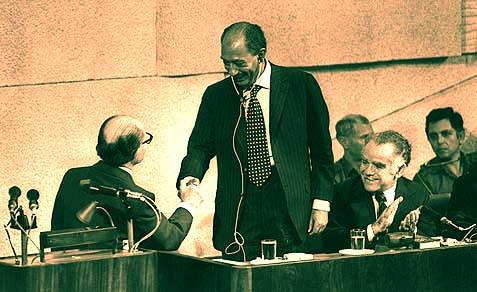 Egyptian President Anwar Sadat shaking hands with Prime Minister Menachem Begin, with the Knesset Speaker Yitzhak Shamir looking on.