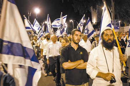 A crowd carries Israeli flags during a march around the walls of Jerusalem on Monday night, the eve of Tisha B'Av, the darkest day on the Jewish calendar. This year's fast came at a time of increasingly bitter infighting among Israel's Orthodox Jews.