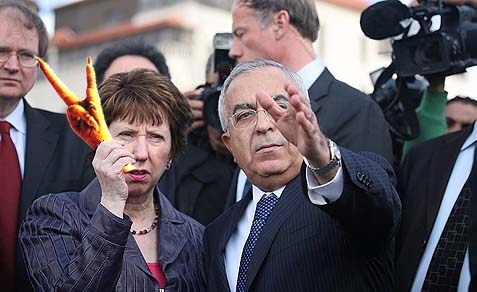 EU Foreign Policy Chief Catherine Ashton marking the V sign for Victory with a chicken leg, standing next to former Palestinian prime minister Salam Fayyad, January 6, 2011.