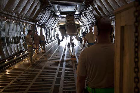 An F/A-18 Super Hornet aircraft is being loaded onto a C-5 Galaxy aircraft. U.S. Air Force photo by Senior Airman David Carbajal
