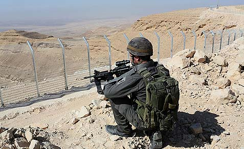 An IDF soldierstanding guard at the newly built security fence on the border between Egypt and Israel.