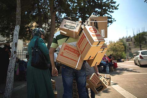 A man carrying gas mask kits which he collected from a distribution center in Jerusalem, August 29, 2013.