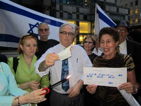 Richard Allen (center), head of JCC Watch, holds a burning check at a rally on Sept. 12 during which his group as well as Americans for a Safe Israel urged the cessation of Jewish donations to the UJA-Federation of New York, due to federation's lack of funding guidelines on Israel. (Credit: JCC Watch/AFSI)