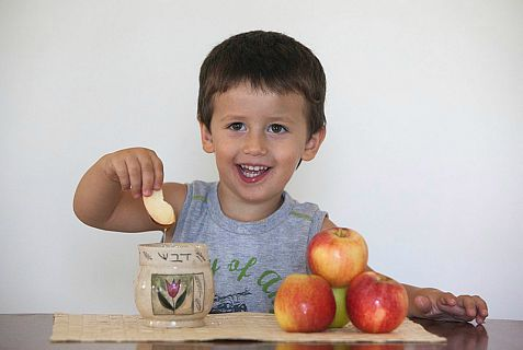Young Israeli boy dip apple in honey in tradition with the Rosh HaShanah New Year holiday