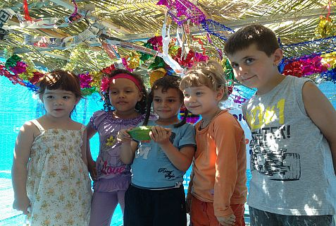 recent immigrants to Israel pose in the sukkah they helped build at The Jewish Agency's Ye'elim Immigrant Absorption Center in Be'er Sheva.