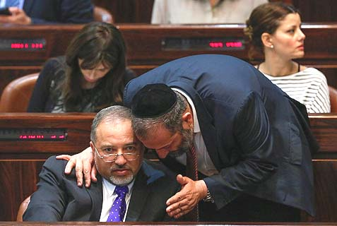 Shas party Chairman MK Aryeh Deri hovering over the shoulder of Israel Beiteinu party leader MK Avigdor Liberman in the Knesset. Deri is basing his entire strategy for a return to government on Liebrman.