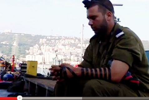 Religious IDF sailor starts out his day at sea with tefillin.