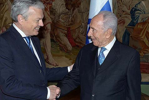 President Shimon Peres shaking hands enthusiastically with Belgium's Foreign Minister Didier Reynders in Brussels.