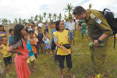 IDF rescue worker speaks with local residents at a disaster zone in the Philippines.