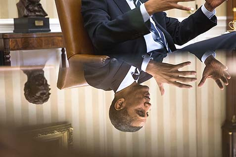 President Barack Obama is reflected in a glass table during a meeting in the Oval Office.
