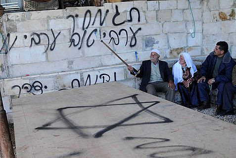 "Who did it? Arabs sit against a wall under racist graffiti reading ""Price tag"", ""A good Arab is a dead Arab"" and ""Revenge from Yitzhar."""