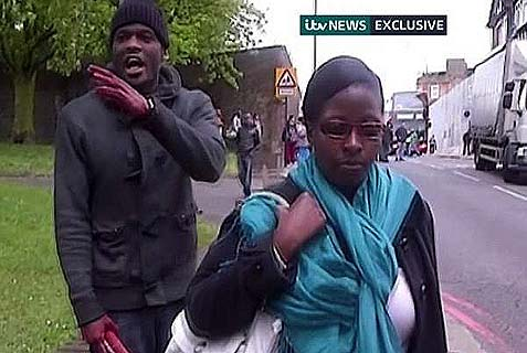 Michael Adebolajo, holding a knife in his bloody-covered hand, rants in front of a camera near where he murdered Lee Rigby, whose body can be seen lying in the road.