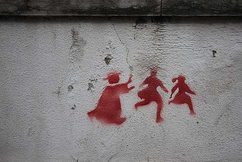 Graffiti on a wall in Lisbon depicting a priest chasing two children, denouncing the child abuse that rocked the Catholic Church.