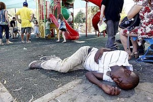 An African illegal sleeping on the ground in a south Tel Aviv playground. Photo credit: Abir Sultan/Flash 90