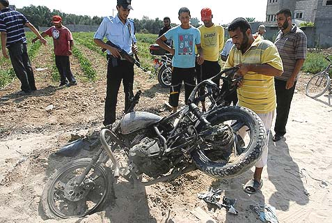 Palestinians inspect at a motorcycle that was hit in an Israeli air strike in Dir al-Balah in the central Gaza Strip in 2012, similar to this morning's attack.