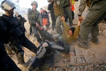 Police manhandle a youth in expulsion from the Hebron Peace house in December 2008.