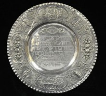 A classic Seder plate, silver with the order of the service at center and scenes from the Haggadah on the rim. German, circa 1890.