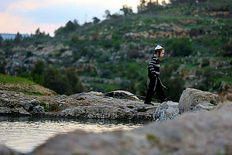 A Jewish child walks beside a stream near Jerusalem. The water from the stream is used to make matzo for Pesach.