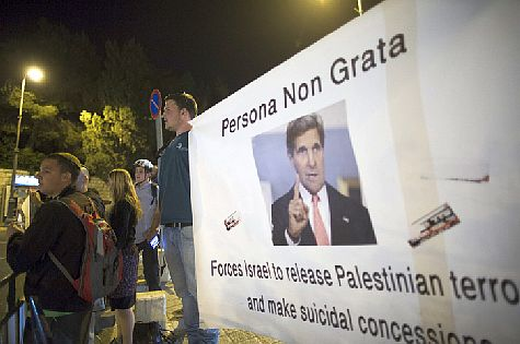 Israeli protester hold up banners as they protest against US Secretary of State John Kerry, in Jerusalem, March 31, 2014.