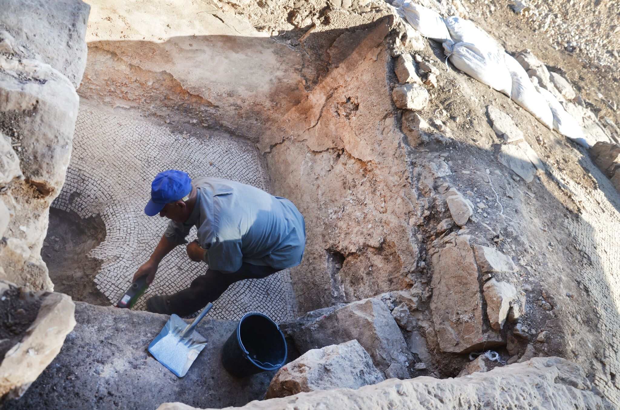 A laborer in the excavation cleaning a collecting vat of a winepress that was revealed at the site.