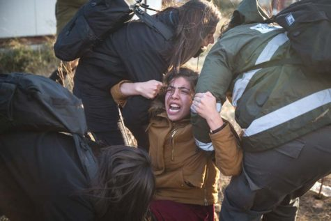 A young woman is hauled to an evacuation bus in Amona, February 1, 2017. According to Honenu, as soon as the media had left, the serious beatings started.