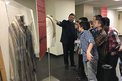 Students from Yeshiva Tifereth Moshe viewing the uniform and the tzitzis during their visit to Amud Aish.