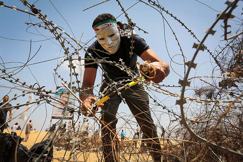 Arab terrorist cuts barbed wire during clashes with Israeli forces along the border with the Gaza strip