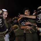 Israeli soldiers dance with Torah scrolls.