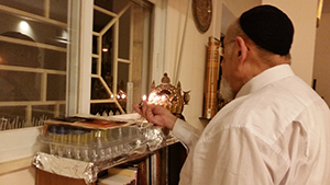 The author's husband lighting the menorah.