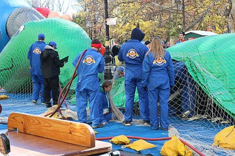 Staff from the Macy's Thanksgiving Day Parade help inflate the massive balloons for the giant floats.
