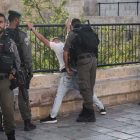 Israeli Border Guard police checking a young Arab man outside Damascus Gate in Jerusalem's Old City.