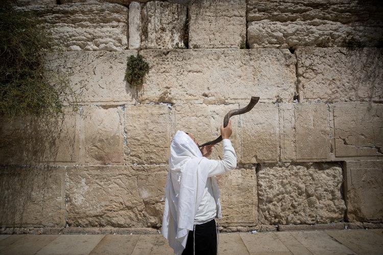 An ultra orthodox Jewish man blows a shofar at the Western Wall in Jerusalem's Old City