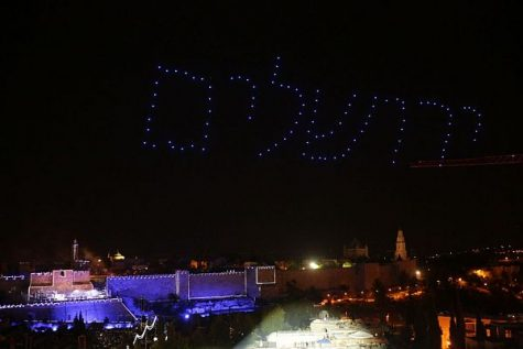 "Blue lights in the sky spell the name ""Jerusalem"" in Hebrew over the glowing walls of the Old City of Jerusalem below."