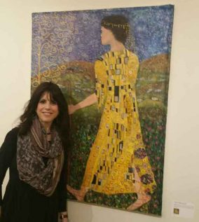 "Esty Frankel-Fersel stands in front of her reimagined canvas she titled, ""Yosef and His Coat of Many Colors,"" a painting she adapted from Gustav Klimt's original and more immodest image called, ""The Kiss."""