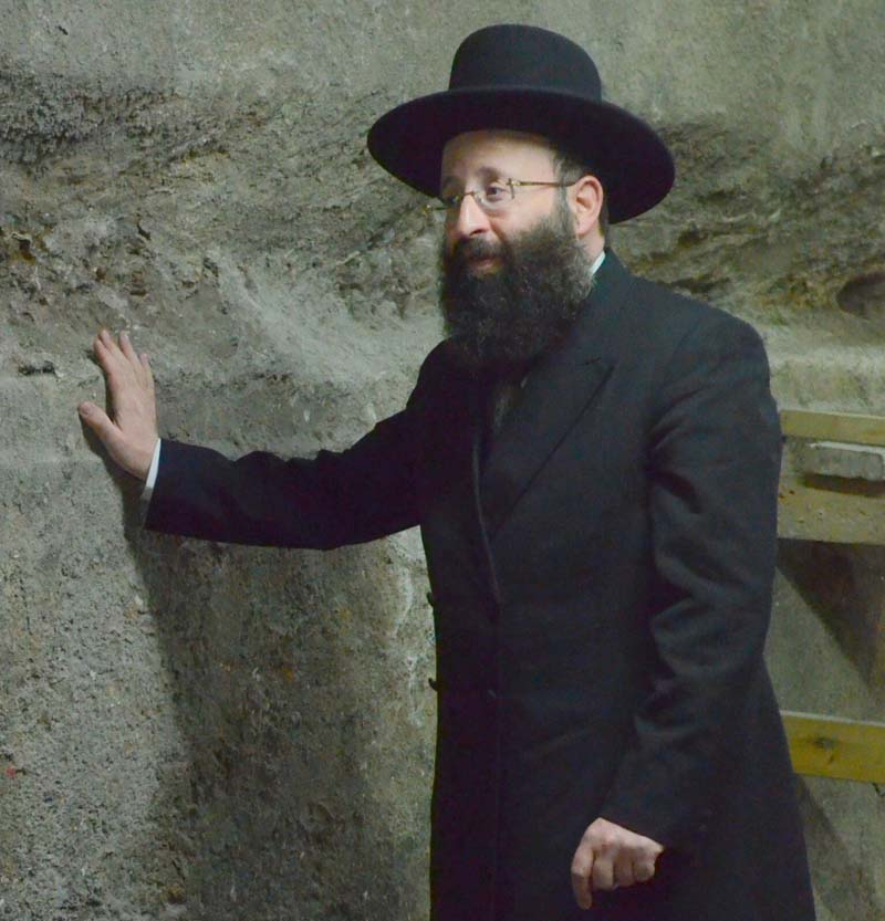 Rabbi Shmuel Rabinovitch, Rabbi of the Western Wall and the holy places, touching one of the Western Wall stones discovered in the excavation. / Photo credit: Yaniv Berman, courtesy of the Israel Antiquities Authority