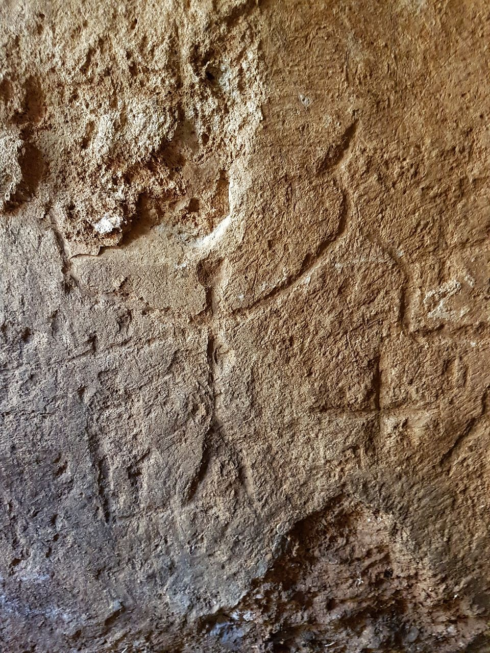 Engravings on the walls: Human figures and crosses.