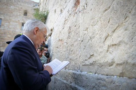 U.S. Ambassador David Melech Friedman prays from a Hebrew prayer book at the Western Wall before starting his term in Israel under the Trump administration