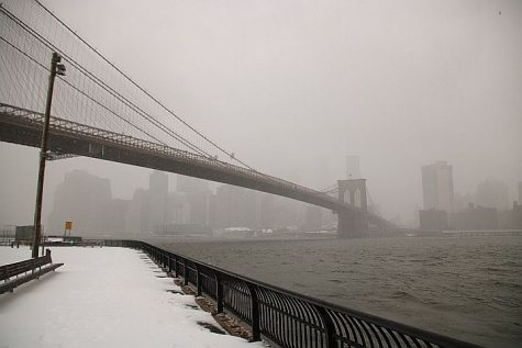 The Brooklyn Bridge and the East River during a winter storm from the Manhattan shoreline.