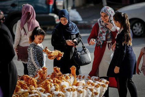 Buying stuffed dolls of sheep at a market ahead of the Eid al-Adha festival in the city of Hebron, on August 21, 2017.