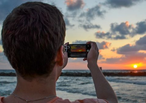 A young man captures the sunset over the Mediterranean Sea with his cell phone in Tel Aviv